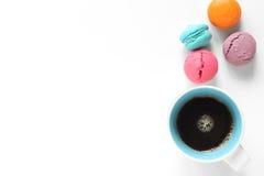 Macarons e una tazza di caffè su bianco Fotografie Stock Libere da Diritti