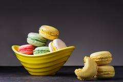 Macarons empilhou em um prato amarelo imagens de stock