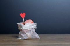 Macarons en una bolsa de papel con el corazón de papel Imágenes de archivo libres de regalías