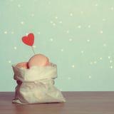 Macarons en una bolsa de papel con el corazón de papel fotografía de archivo libre de regalías
