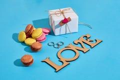 Macarons et boîte-cadeau sur un fond bleu avec le lov des mots I Photo stock