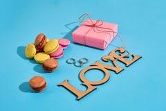 Macarons et boîte-cadeau sur un fond bleu avec le lov des mots I Photos stock