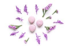 Macarons et fleurs pour le petit déjeuner léger sur la vue supérieure de fond blanc de bureau Images libres de droits