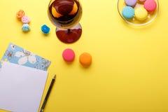 Macarons et verre colorés sur la table bleue avec la carte postale au-dessus du fond jaune Photos stock