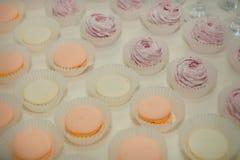 macarons et zéphyr dans les rangées sur la table Photos libres de droits