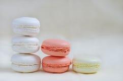 Macarons färgade i pastellfärgade färger som står kolonner Arkivfoton