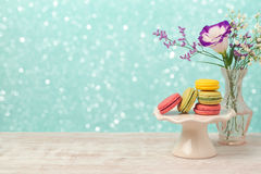 Macarons with flowers on wooden table over bokeh holiday background Stock Images