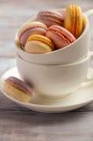 Macarons français colorés dans la tasse blanche sur le fond en bois Photo libre de droits