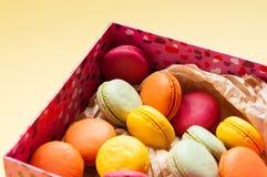 Macarons français colorés sur le fond jaune Image libre de droits