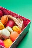 Macarons français colorés sur le fond vert Photos stock
