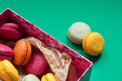 Macarons français colorés sur le fond vert Image libre de droits