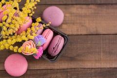 Macarons français doux dans un paquet avec les fleurs et la mimosa photographie stock libre de droits