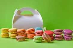 Macarons français et un boîtier blanc au-dessus d'un fond vert photo stock