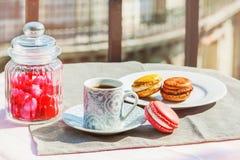Macarons français et une tasse d'expresso sur un balcon Photos libres de droits