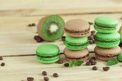 Macarons français verts et bruns avec le kiwi, les grains de café et les décorations de menthes Photos stock