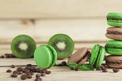 Macarons français verts et bruns avec le kiwi, les grains de café et les décorations de menthes Images libres de droits