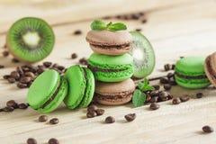 Macarons français verts et bruns avec le kiwi, les grains de café et les décorations de menthes Photographie stock