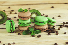 Macarons français verts et bruns avec le kiwi, les grains de café et les décorations de menthes Image stock