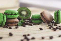 Macarons français verts et bruns avec le kiwi, les grains de café et les décorations de menthes Images stock