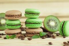 Macarons français verts et bruns avec le kiwi, les grains de café et les décorations de menthes Photo stock