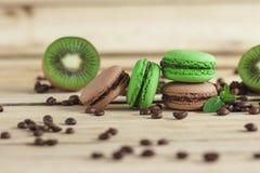Macarons français verts et bruns avec le kiwi, les grains de café et les décorations de menthes Photos libres de droits