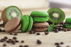 Macarons français verts et bruns avec le kiwi, les grains de café et les décorations de menthes Photo libre de droits