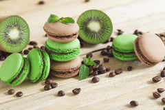 Macarons français verts et bruns avec le kiwi, les grains de café et les décorations de menthes Image libre de droits