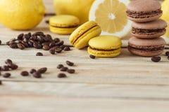 Macarons franceses amarillos y marrones con los limones y los granos de café en el tablero de madera Fotos de archivo libres de regalías