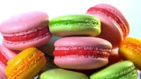 Macarons franceses - cookies da merengue com enchimento do ganache ou do buttercream Bolinhos de amêndoa coloridos que gerenciem, filme