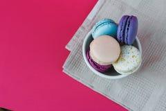Macarons franceses en taza Bisquits coloridos dulces Visión superior Fondo de las rosas fuertes Mantel Imagenes de archivo