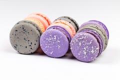 Macarons franceses o macarrones púrpuras, grises y rosados, alineados en vista lateral del primer fotografía de archivo libre de regalías