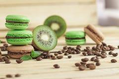 Macarons franceses verdes y marrones con el kiwi, los granos de café y las decoraciones de las mentas imágenes de archivo libres de regalías
