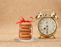 Macarons. Gold stylish alarm clock, breakfast time Royalty Free Stock Photo