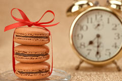Macarons. Gold stylish alarm clock, breakfast time Royalty Free Stock Photos