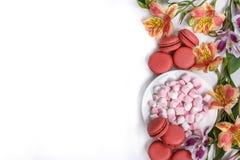 Macarons, guimauves dans la cuvette et Alstroemeria de fleurs sur une table blanche Image stock