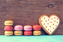 Macarons and heart-shaped cookie on a blue rustic surface. Some appetizing macarons with different colors and flavors and a homemade heart-shaped cookie on a Royalty Free Stock Photography