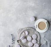 Macarons i bunke och på tabellen med koppen kaffe och lavendel Royaltyfri Foto
