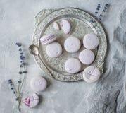 Macarons i bunke och på tabellen med koppen och lavendel Arkivfoto