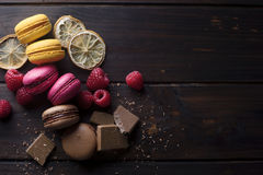 Macarons with ingredients over a dark wood table. Group of lemon, raspberry and chocolate macarons with their ingredients placed over a dark wood table Royalty Free Stock Images