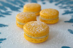 Macarons with lemonfilling 2. Four yellow macarons with a lemon-mint-filling on blue and white background Stock Photos