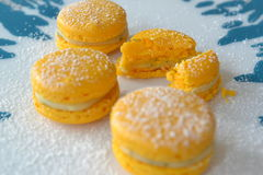 Macarons with lemonfilling 3. Four yellow macarons with a lemon-mint-filling on blue and white background Royalty Free Stock Images