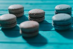 Macarons or macaroons lie on a turquoise wooden background.  Royalty Free Stock Photo