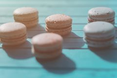 Macarons or macaroons lie on a turquoise wooden background, toning.  Royalty Free Stock Image