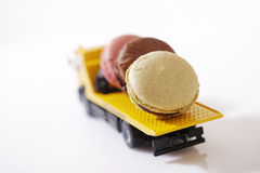 Macarons in a miniature car Stock Photos
