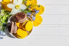 Macarons o hermoso dulce del postre de los macarrones a comer postres del chocolate y del limón en una tabla de madera blanca Pos foto de archivo libre de regalías