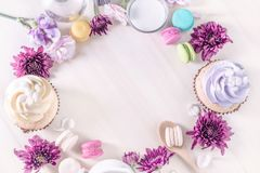 Macarons o macarrones y magdalenas con leche en un pastel del vintage imagen de archivo