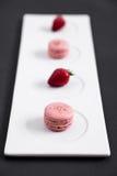 Macarons och jordgubbar på en platta royaltyfri foto