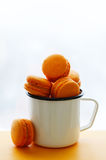 Macarons of orange color in enamel cup Stock Image