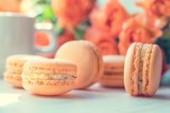 Macarons oranges et petites roses fraîches Image libre de droits