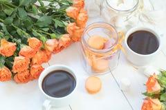Macarons oranges, tasse de café et roses fraîches Photo libre de droits